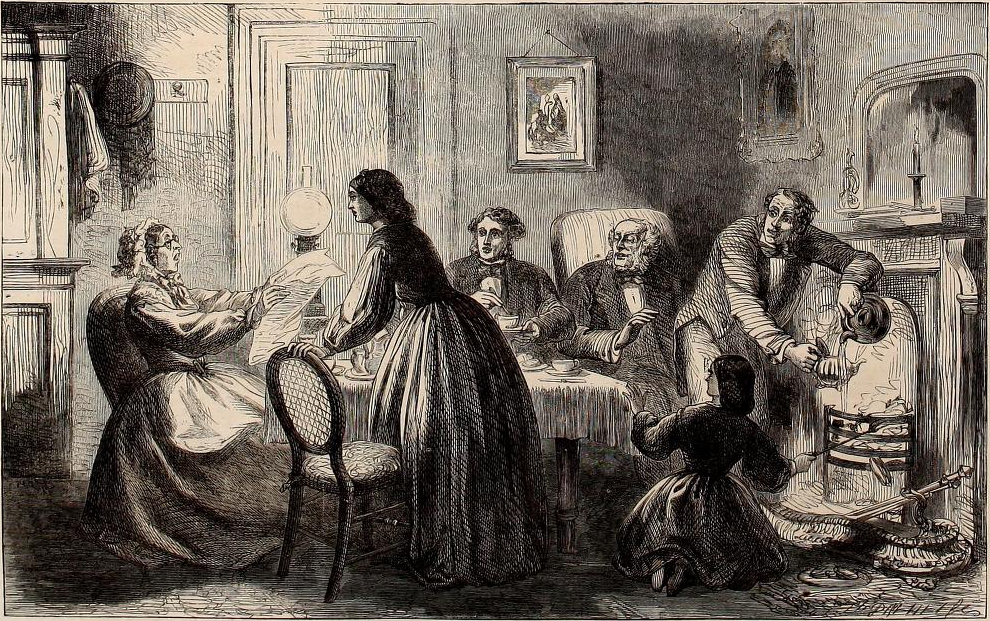 A family gathered around the table with an older woman at the head reading from a piece of paper. All look riveted.