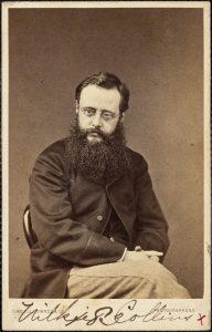 Black and white photograph of Wilkie Collins: a man with short hair, glasses and a bushy beard.