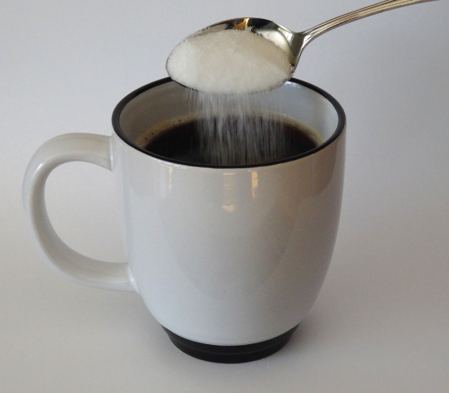 A picture is shown of sugar being poured from a spoon into a cup.