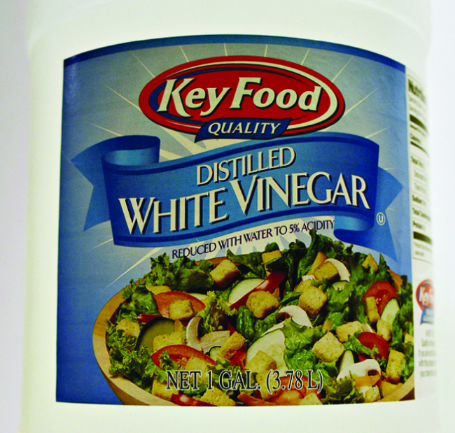"""A label on a container is shown. The label has a picture of a salad with the words """"Distilled White Vinegar,"""" and, """"Reduced with water to 5% acidity,"""" written above it."""
