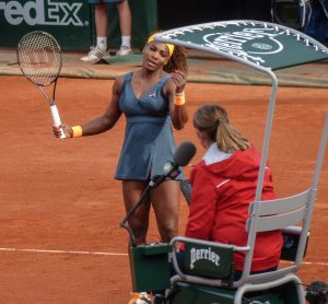 Serena Williams on clay court talking with umpire.